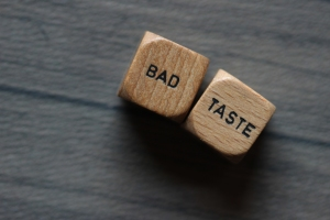 """Bad taste"" printed on two wood dice against a wood grey background"