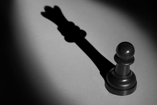 Chess Pawn Standing In A Spotlight That Make A Shadow Of Queen A